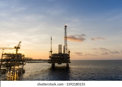 Silhouette of an oil production platform at oil field during sunset