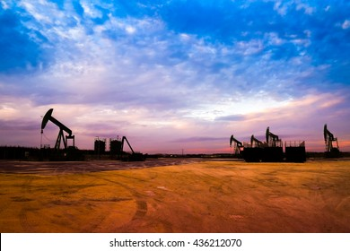 Silhouette of Oil pumps at oil field with nice sunset sky background