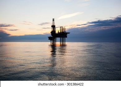 Silhouette of oil rig at sunset