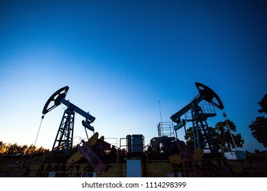 silhouette of oil rigs against the background of the twilight sky