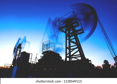 silhouette of oil rigs against the background of the twilight sky, long exposure, retro toned