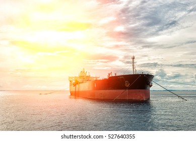 The silhouette of an oil tanker at sunset.