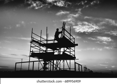 Silhouette of oilfield worker climbing on a scaffold board at sunset - Black and white edit