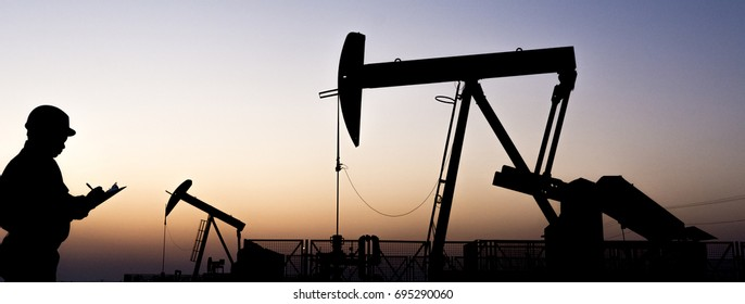 Silhouette of oilfield worker and crude oil pump in oilfield at sunset blue hour
