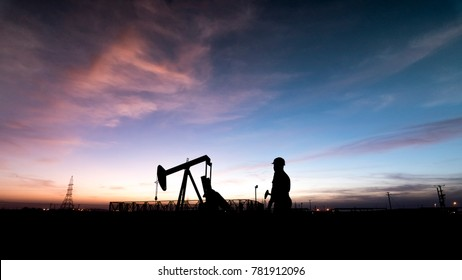 Silhouette of oilfield worker at  crude oil pump in the oilfield at sunset.
