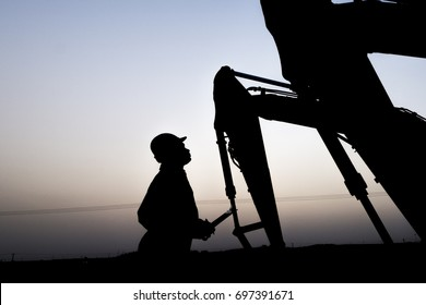 Silhouette of oilfield worker inspecting the excavator in oilfield