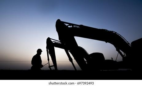 Silhouette of oilfield worker inspecting the excavator in oilfield