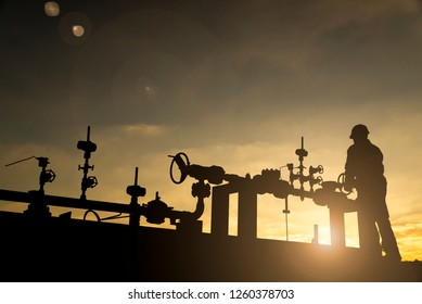 Silhouette of the oilfield worker monitoring the manifold valves in the oilfield