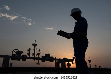 Silhouette of a oilfield worker monitoring valves at sunset.