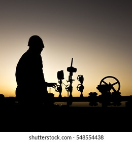 Silhouette of oilfield worker monitoring valves at sunset.