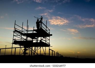 Silhouette of oilfield worker on a scaffolding in oilfield at sunset