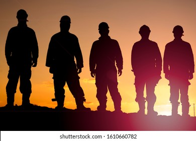 Silhouette of oilfield workers at sunset in oilfield