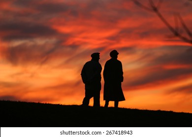 Silhouette of an old couple walking at sunset