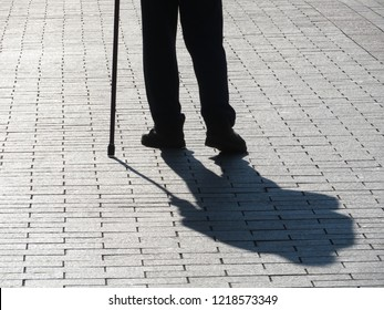 Silhouette of old man walking with a cane, long shadow on pavement. Concept for disability, blind man, old age, diseases of the spine, senior adult