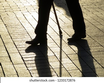 Silhouette of old man walking with a cane, long shadow on pavement. Concept for disability, old age, sick person, dramatic life