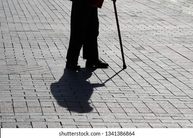 Silhouette of old person walking with a cane, long shadow on pavement. Concept for disability, old age, limping or blind man, diseases of the spine, elderly people