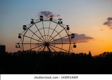 Silhouette of old soviet Ferris wheel against sunset sky