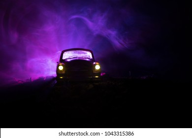 Silhouette of old vintage car in dark foggy toned background with glowing lights in low light, or silhouette of old crime car dark background. Selective focus