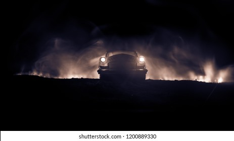 Silhouette of old vintage car in dark foggy toned background with glowing lights in low light. Selective focus