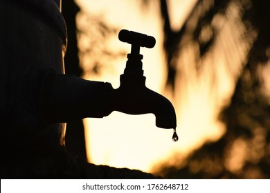 Silhouette of old vintage metal tap leaking last water droplet . alone in outdoor natural environment during golden hour of sunrise , water shortage , crisis , scarcity