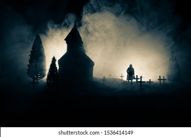 Silhouette of old woman with a cane walking at cemetery at night. Horror Halloween concept. Artwork decoration with light and fog. Selective focus