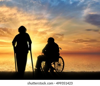 Silhouette of an old woman on crutches and elderly man in a wheelchair on a background of sea sunset. Concept of disability and old age