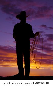 A silhouette of a older cowboy holding on to his rope.
