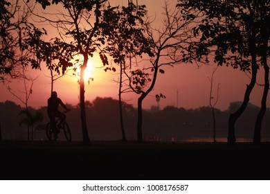 silhouette of the oldman riding a road bike at sunset.