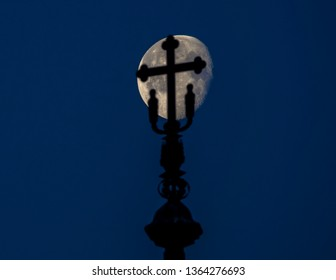 Silhouette on the top of a church with the moon in the background