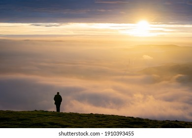 Silhouette of one lone man stood on edge of mountain peak top above clouds as fog mist and cloud inversion gathers watching the sun rise with a beautiful orange sunlight sky