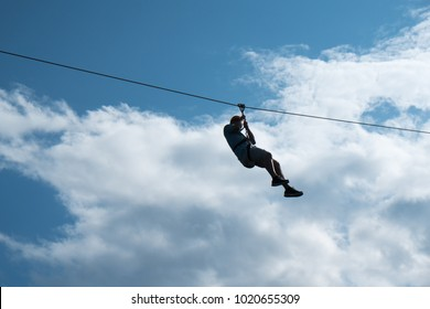 Silhouette of one man riding a zip line, harness and helmet, black silhouette against a blue sky and clouds. Extreme sports, riding a zip line high above the earth.