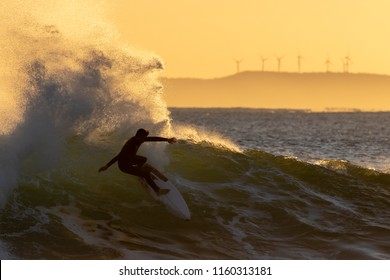The silhouette of one surfer at sunrise at Jeffreys Bay in South Africa. The wave is backlit by the rising sun with wind turbines on the horizon