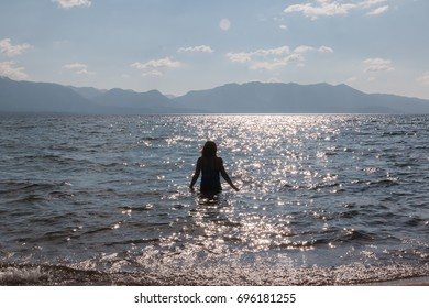 Silhouette of One Young Girl With Raised Arms in the Water at the Beach