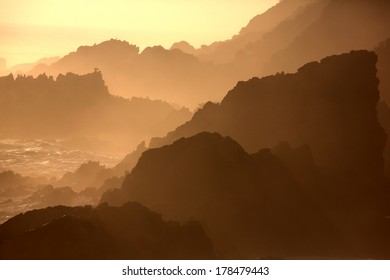 Silhouette outline of the rugged coastline in South Africa at sunset