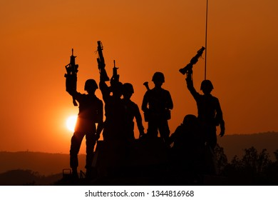 silhouette and over the sunrise background cannon soldiers team standing holding gun in Thailand