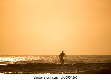 silhouette of paddle boarder standing on SUP over the sunrise