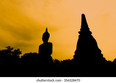 Silhouette pagoda and statue at sunset in Sukhothai Historical Park