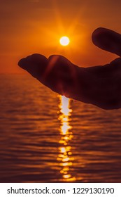 silhouette of a palm of a hand almost touching the setting sun over an ocean. The rays of the sun can be seen shining over the hand and rippling in the water of the sea