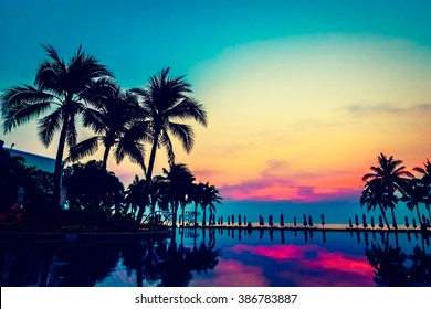 Silhouette palm tree with umbrella and chair around beautiful luxury swimming pool in hotel resort at Sunset time - Vintage Filter and Boost up Color Processing