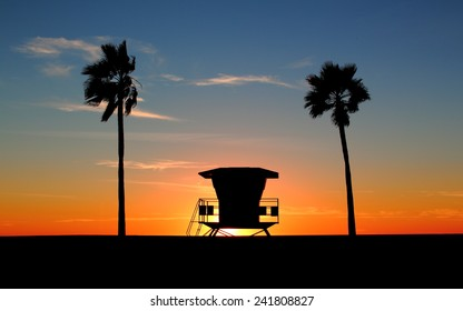 Silhouette of palm trees and classic California life guard station. Sun is setting as day turns into dusk/night and orange, red, yellow colors  fill the sky