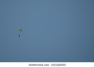 Silhouette of parachutist flying on parachute  in blue clear sky, sun flares.Solar lens flare with paratrooper, parachuters on clear sky with The Sun in the daytime.