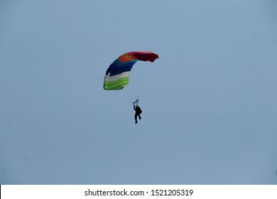 Silhouette of parachutist flying on parachute  in blue clear sky. Paratrooper, parachuters on clear sky with The Sun in the daytime.