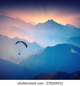 Silhouette of paraglide flying over the high mountains in a light of sunrise. Ukrainian Carpathian valley.