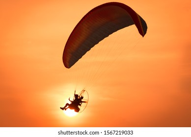Silhouette of the Paramotor control flying through soft sunlight sunset sky