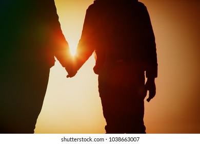 silhouette of parent and child holding hands at sunset