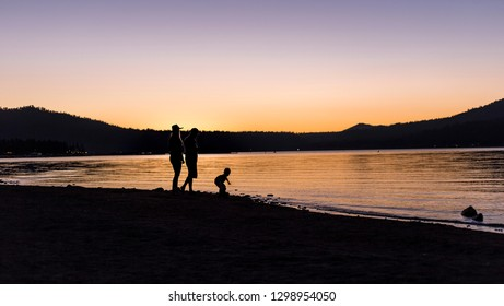 Silhouette of parents with a child watching the sunset over a lake.  The family is hiking or camping outdoors.