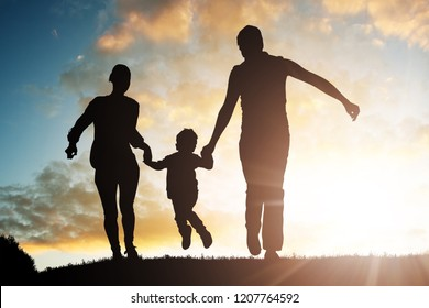 Silhouette Of Parents Having Fun With Their Child At Sunset
