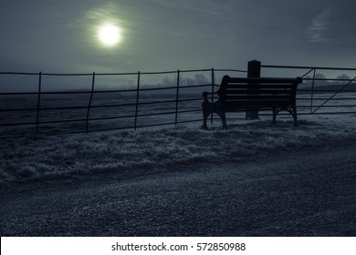 Silhouette of Park Bench, Railings and Frosty Grass at Sunrise Over Open Fields