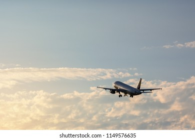 Silhouette of passenger airplane in the air, flying on the cloudy sky.