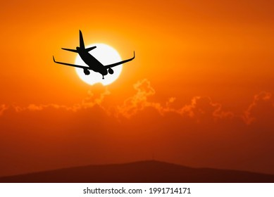 Silhouette of a passenger flight story with tourists landing at the airport. Airplane landing at sunset. passenger plane is landing in the airport runway at early morning at sunrise time